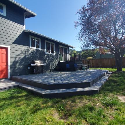 Custom-Decks-ground-level-deck-wrap-around-steps-trex-pebble-gray-trex-winchester-gray-accent-trex-railing-signature-in-black-enclosed-upper-deck-bothell-washington