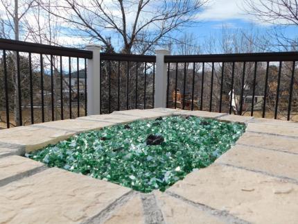 Custom-Decks-colored-glass-filling-burner-area-custom-fire-pit-Aurora-Colorado